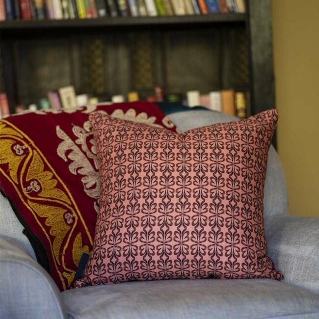 pink botanical throw pillow on a chair in front of bookcase