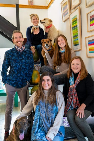 four woman and a man sitting on stairs with their dogs