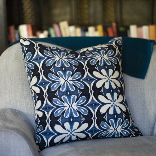 blue and white botanical throw pillow on a chair in front of a bookcase