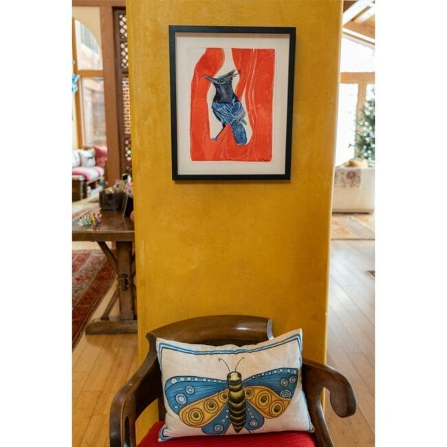 blue and black bird with a black crown on a red organic background watercolor hung up on a wall with a black frame