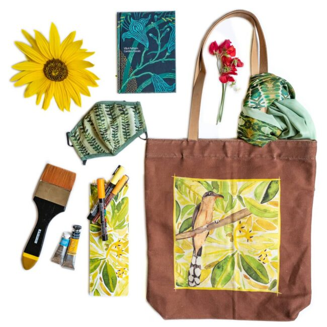 tote bag that has a mangrove cuckoo with green foliage with an assortment of writing utensils, notebooks, mask, flowers and scarf
