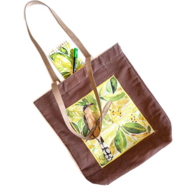 tote bag with a mangrove cuckoo on a brown bag with a green botanical notebook with a green marker