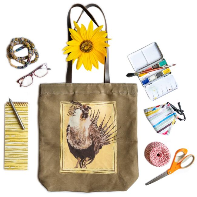 tote bag with a gunnison sage grouse on an olive colored bag with an assortment of notebooks, pencils, paints, masks, string, scissors, glasses and bracelet with a sunflower near the straps