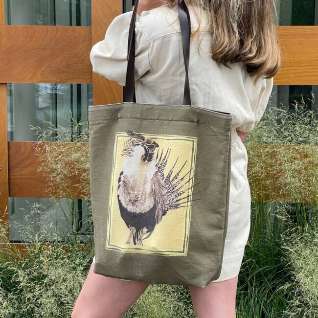 woman standing looking into an art museum with an olive colored bag with a gunnison sage grouse on it