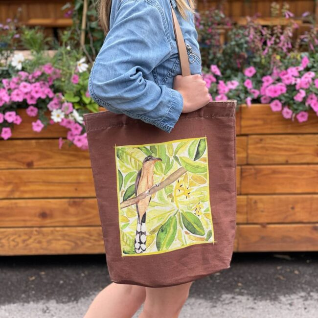 a woman walking in front of a flower box with a jean jacket and a brown bag that has a mangrove cuckoo on it with leaves in the background