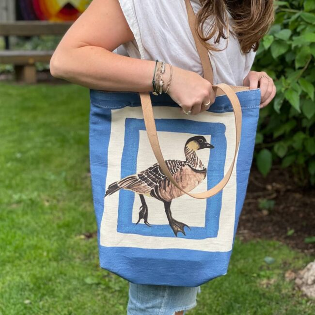 woman in jeans and white blouse standing on a lawn with a blue tote bag that has a hawaiian goose on it
