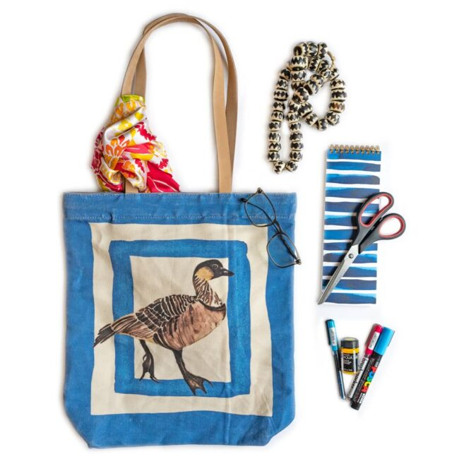blue tote bag with a hawaiian goose and a scarf with an assortment of beads, notebooks, scissors and paint pens