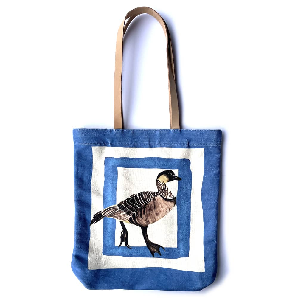 a bright blue tote bag featuring a hawaiian goose that is brown and tan with white squares around him