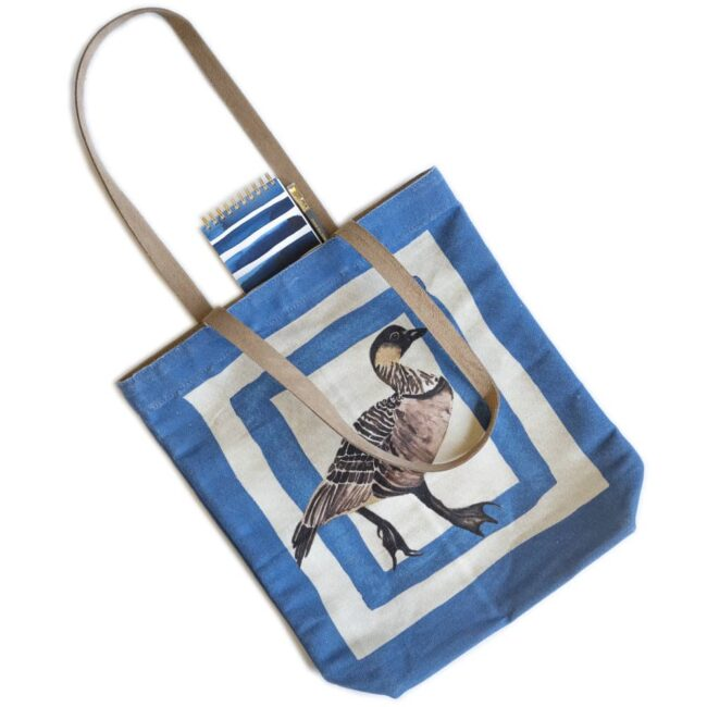 blue tote bag with a hawaiian goose and a blue and white wave notebook and pencil