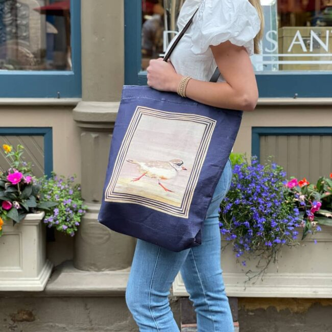 woman standing in front of a colorful flowerbox wearing jeans and a white blouse with a purple tote bag with a piping plover watercolor on it
