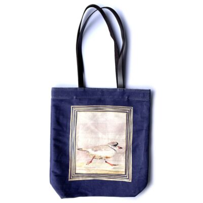 a deep purple tote bag featuring a piping plover running across the sand with a pink and orange sunset