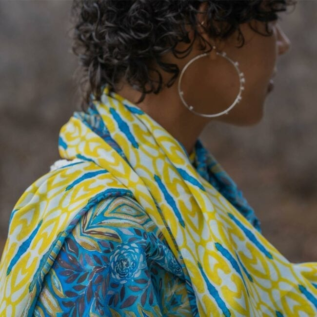Detail shot of model wearing blue and yellow floral scarf with hoop earrings.
