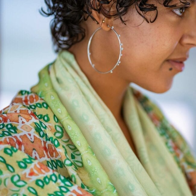 Detail shot of green and red floral scarf around models neck.