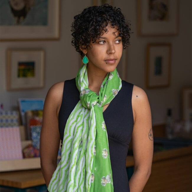 Green hummingbird scarf tied around the neck of model wearing green earrings.