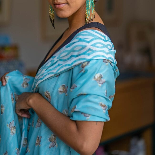 Detail shot of model's shoulder draped in double-sided blue hummingbird and striped scarf.