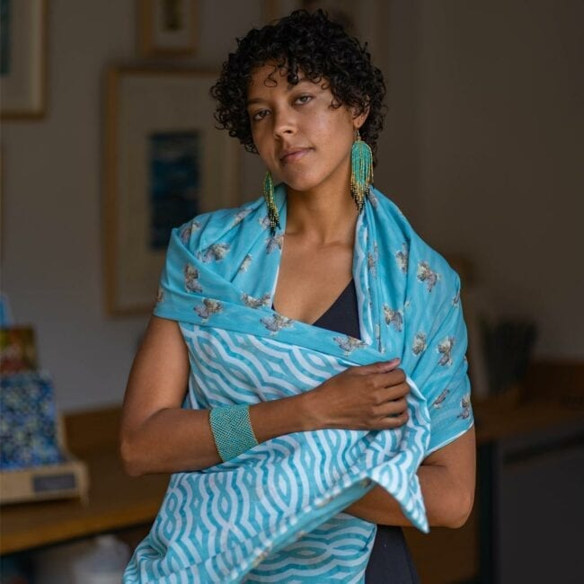 Model wearing turquoise jewelry poses in blue hummingbird and striped double-sided scarf.