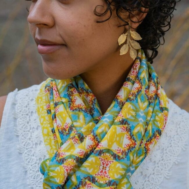 Detail shot of blue, yellow and red scarf on models neck.