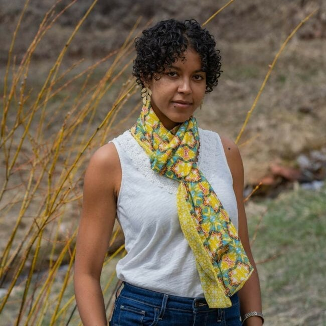 Blue and yellow geometric scarf tied around the neck of model standing outside.