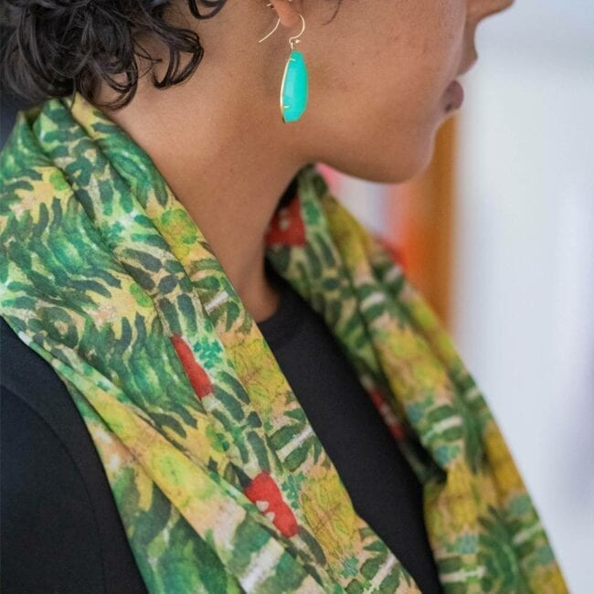 Detail shot of model's neck draped in green and red floral scarf.
