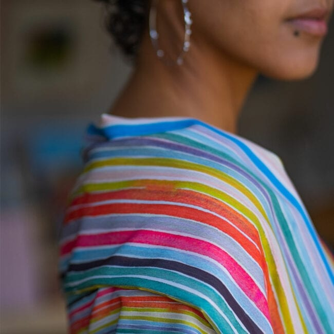 Detail shot of colorful striped scarf draped over shoulder of model.
