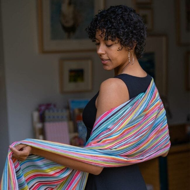 Model wearing colorful striped scarf, looking over shoulder.