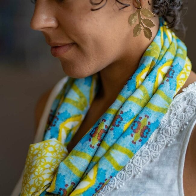 Detail shot of blue and yellow scarf tied around neck of model.