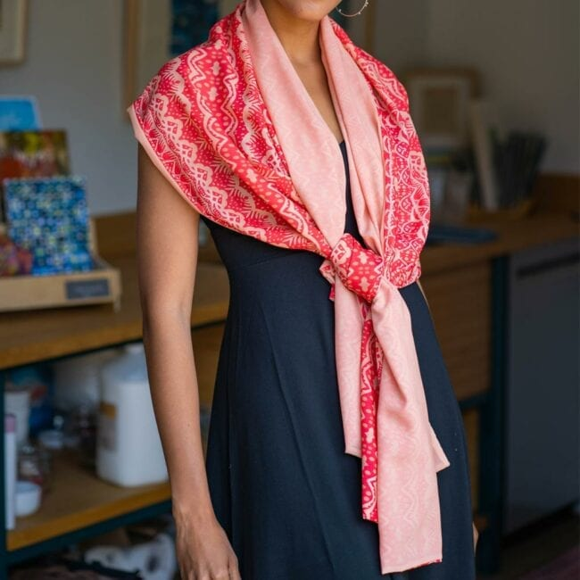 Pink floral scarf tied around neck of model wearing black dress.