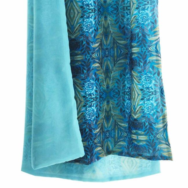 hanging view of a double sided chiffon scarf showing transparency; peacock blue on one side and a lush geometric turquoise and yellow garden inspired pattern on the reverse