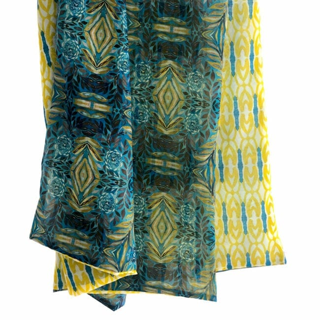 Hanging view of double sided chiffon scarf to show the transparency the front has a blue and yellow lush garden inspired pattern while the back has a yellow geometric pattern with blue accents