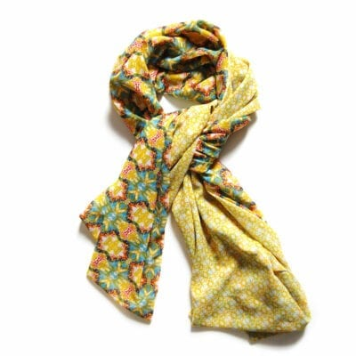 reversible chiffon scarf with turquoise yellow and red garden inspired pattern on one side and yellow geometric pattern on the other.