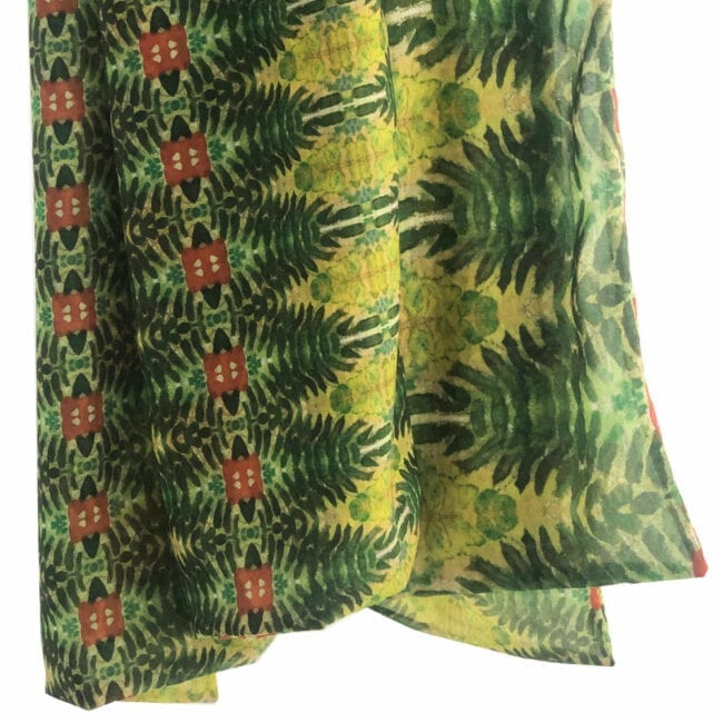 close-up of a green and red botanically patterned scarf