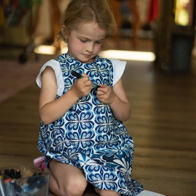 a girls wearing blue and whitebotanical and floral matching smocks putting a pen cap back on