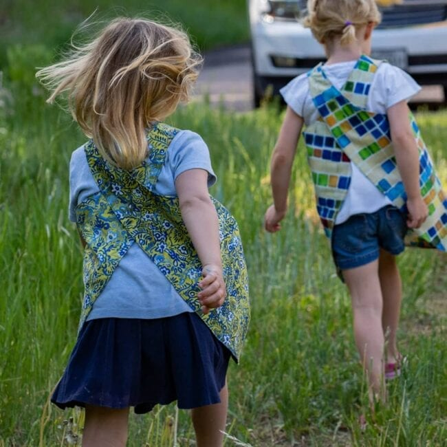 two girls wearing smocks skipping up a path in the grass