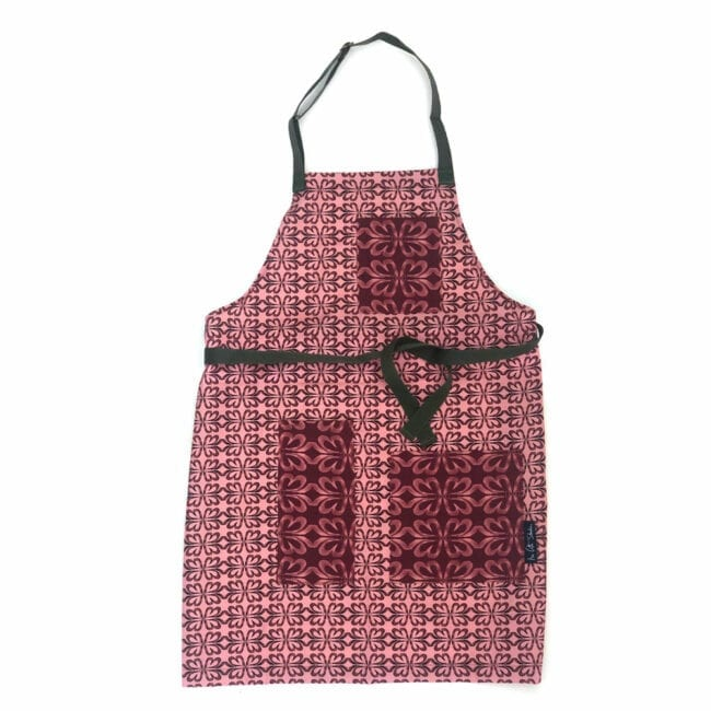 cloverleaf patterned full length apron in a pink color with contrasting cloverleaf patterned pockets in a darker pink with dark green waist strap and neck strap