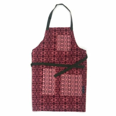 Cloverleaf patterned full length apron laying flat on white background showing three pockets in contrasting cloverleaf pattern and green neck and waist ties
