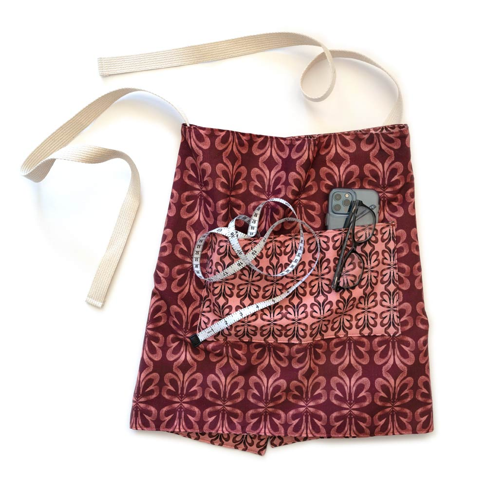 red botanical waist apron with sewing measuring tape, phone, and glasses in the pocket