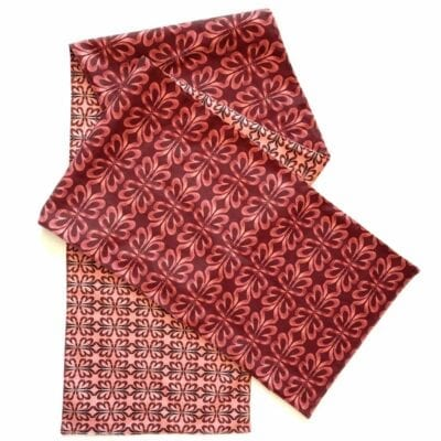 red and pink botanical design of different scales on a long table runner