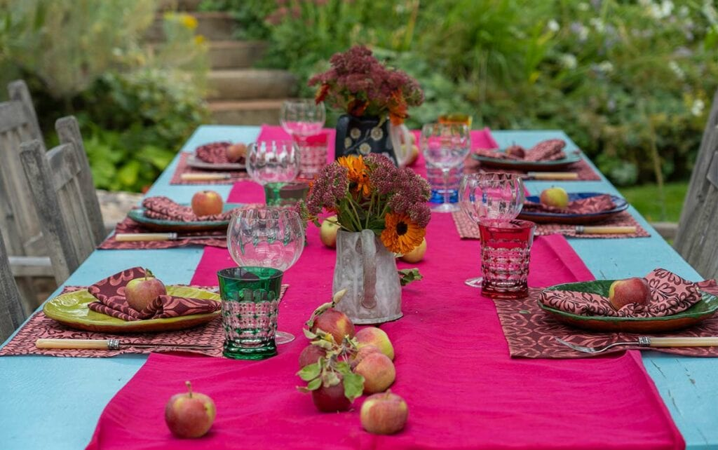 pink and red table setting with turquoise table and green background