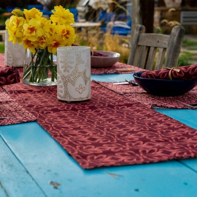 red earth tone botanical designed table runner laid across a table with a white lantern, vase of yellow daffodils, and a small table setting w corresponding placemats and napkins