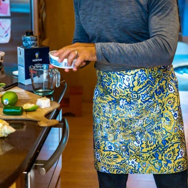 man wearing a gray shirt making a cocktail in a green and blue floral waist apron