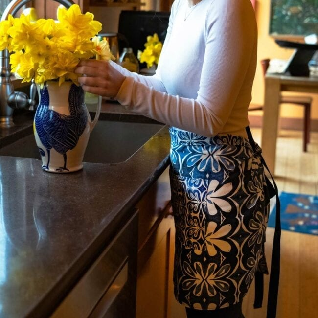 woman in a white shirt putting yellow daffodils in a vase wearing a blue and white botanical waist apron