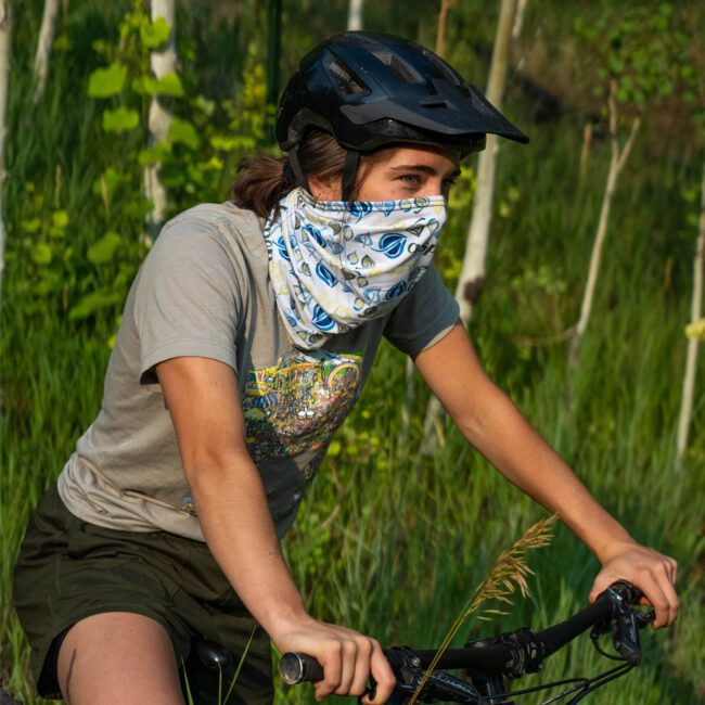 young woman on a bike wearing a white neck gaiter over her nose wearing a helmet