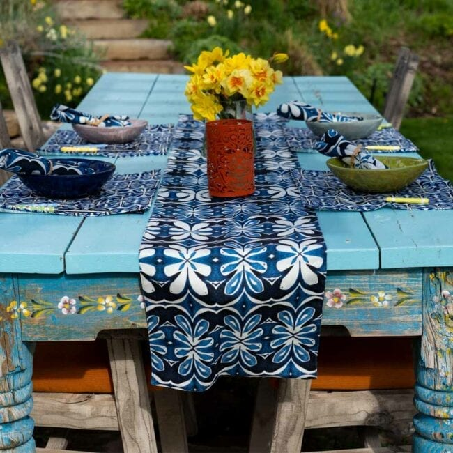 blue and white botanical designed table runner laid across a table with an orange lantern, vase of yellow daffodils, and a small table setting w corresponding placemats and napkins