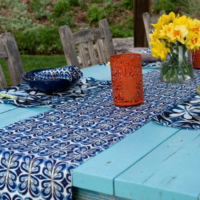 angle view of a blue and white botanical designed table runner laid across a table with an orange lantern, vase of yellow daffodils, and a small table setting w corresponding placemats and napkins