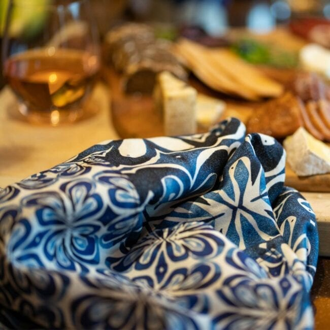 blue and white botanical waist apron laid in front of a charcuterie board