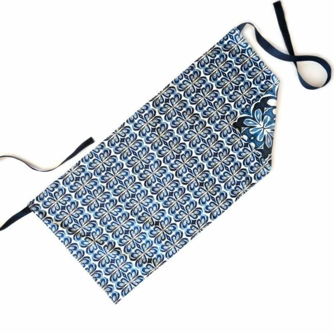 blue and white floral waist apron with blue ties and a reversible, darker design