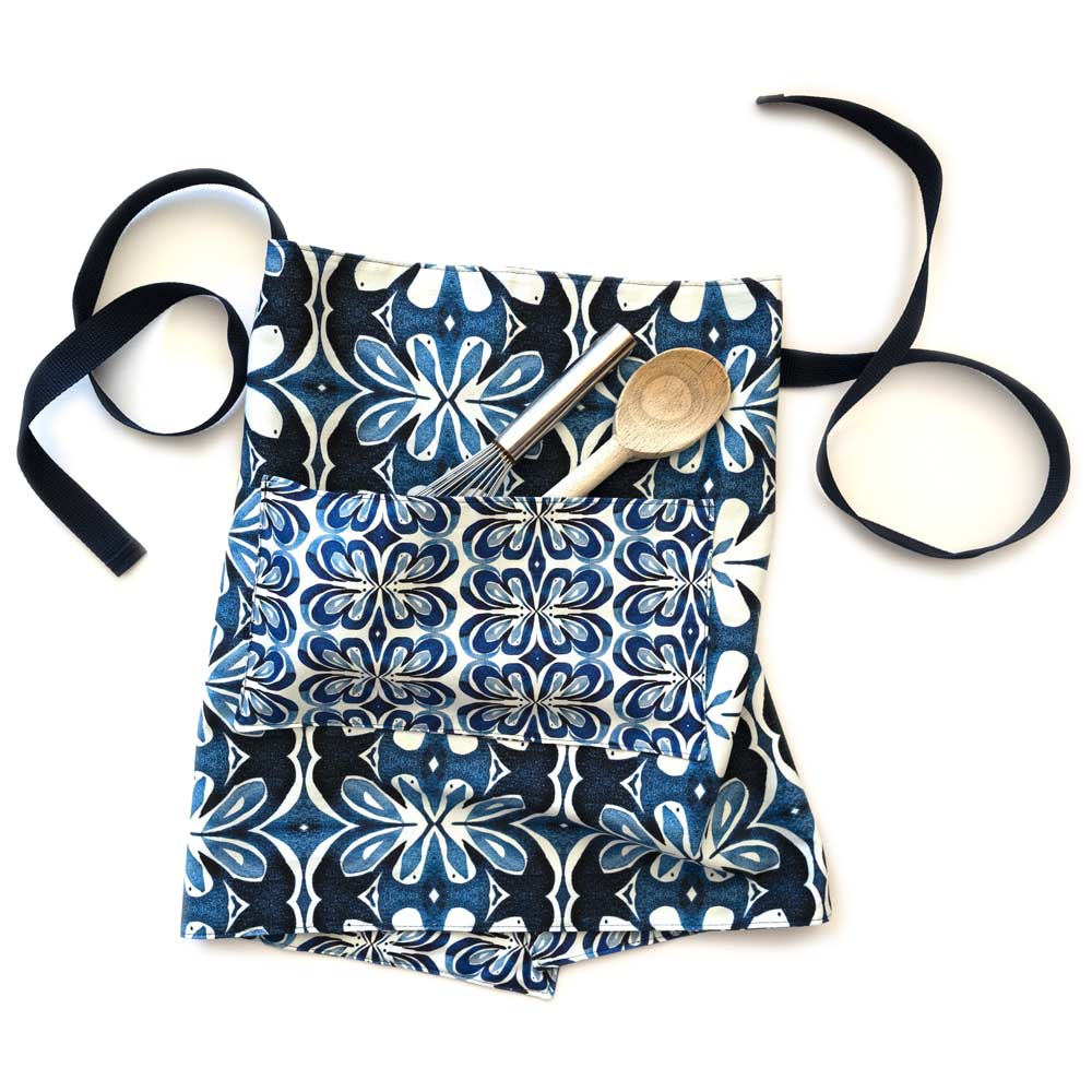 blue and white botanical waist apron with spoon and wisk in the pocket