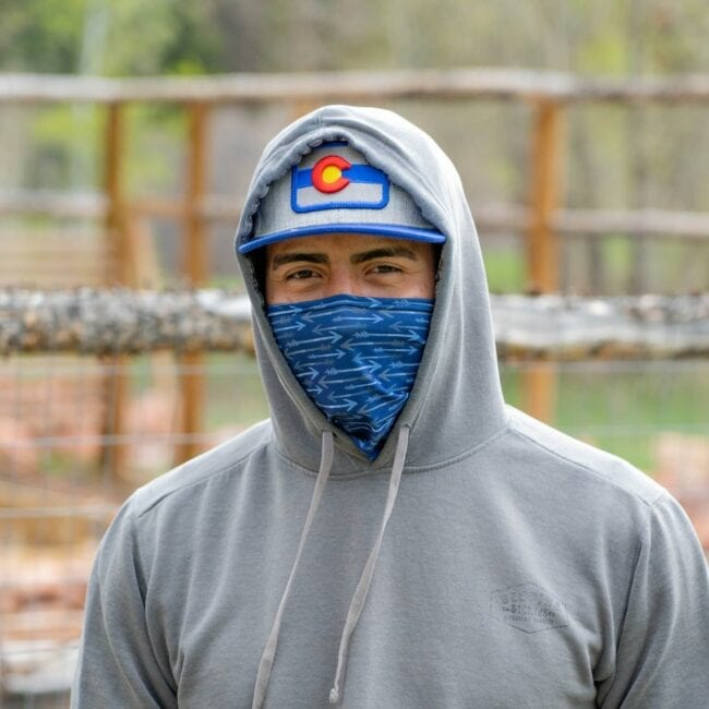 man wearing a navy arrows gaiter with a colorado flag hat and a gray sweather