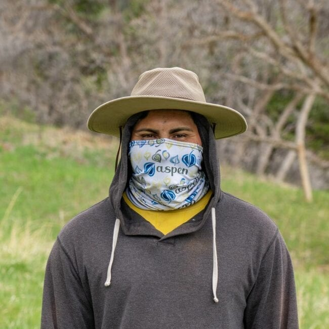 man wearing a white gaiter with blue, green, and yellow leaves that says aspen with a tan hat, yellow shirt, and gray sweater