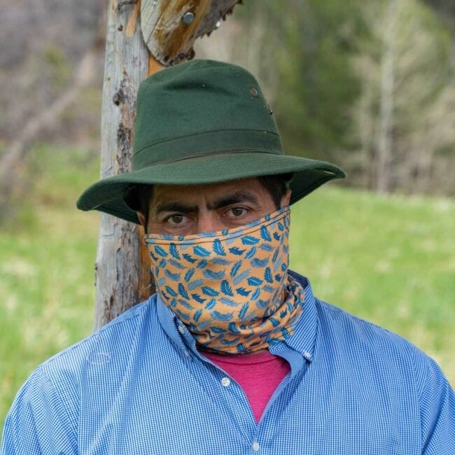 man wearing blue feather gaiter that has an orange background with a green hat, and a red undershirt with a blue shirt over it